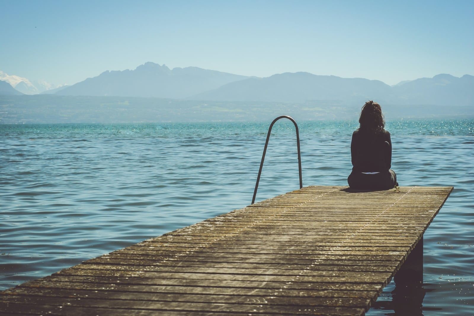 woman sitting on dock looking at water