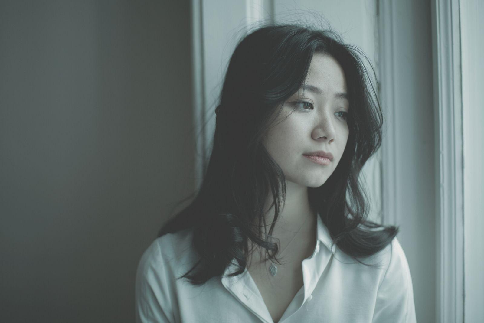 sad pensive woman looking outside thru the window wearing white top