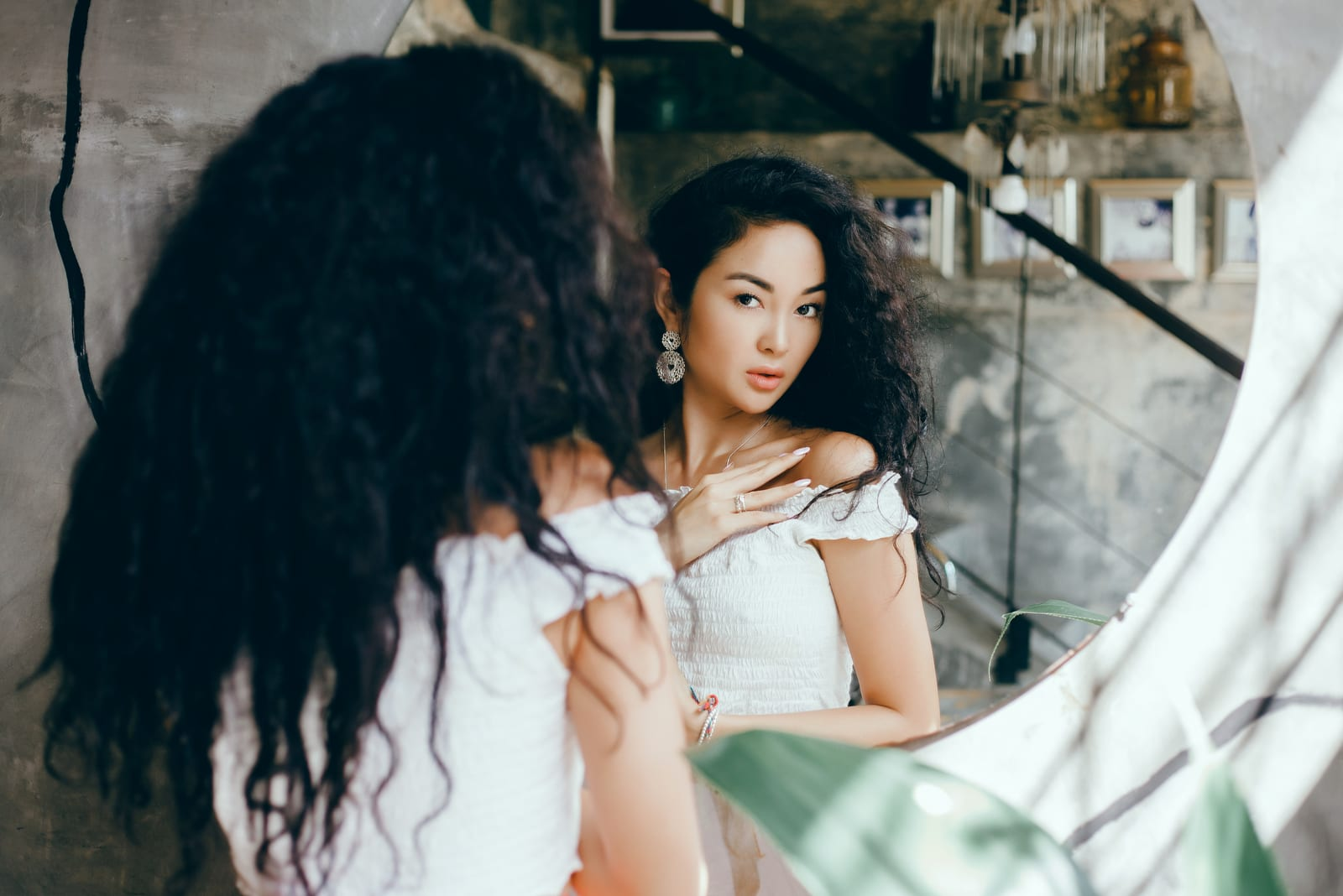 a beautiful asian woman looks in the mirror