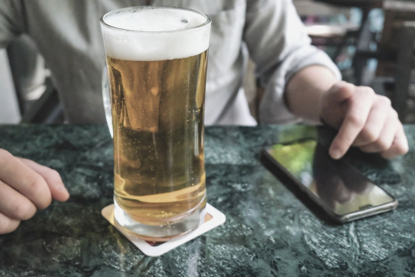 a glass of beer placed on the table with a cropped image of a woman pressing on the keys of the smartphone on the table