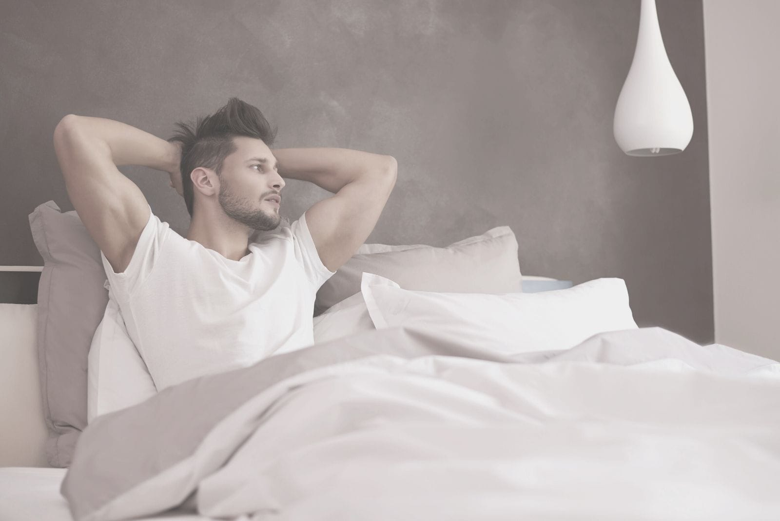 a handsome man in bed thinking deeply placing his hands at the back of his head