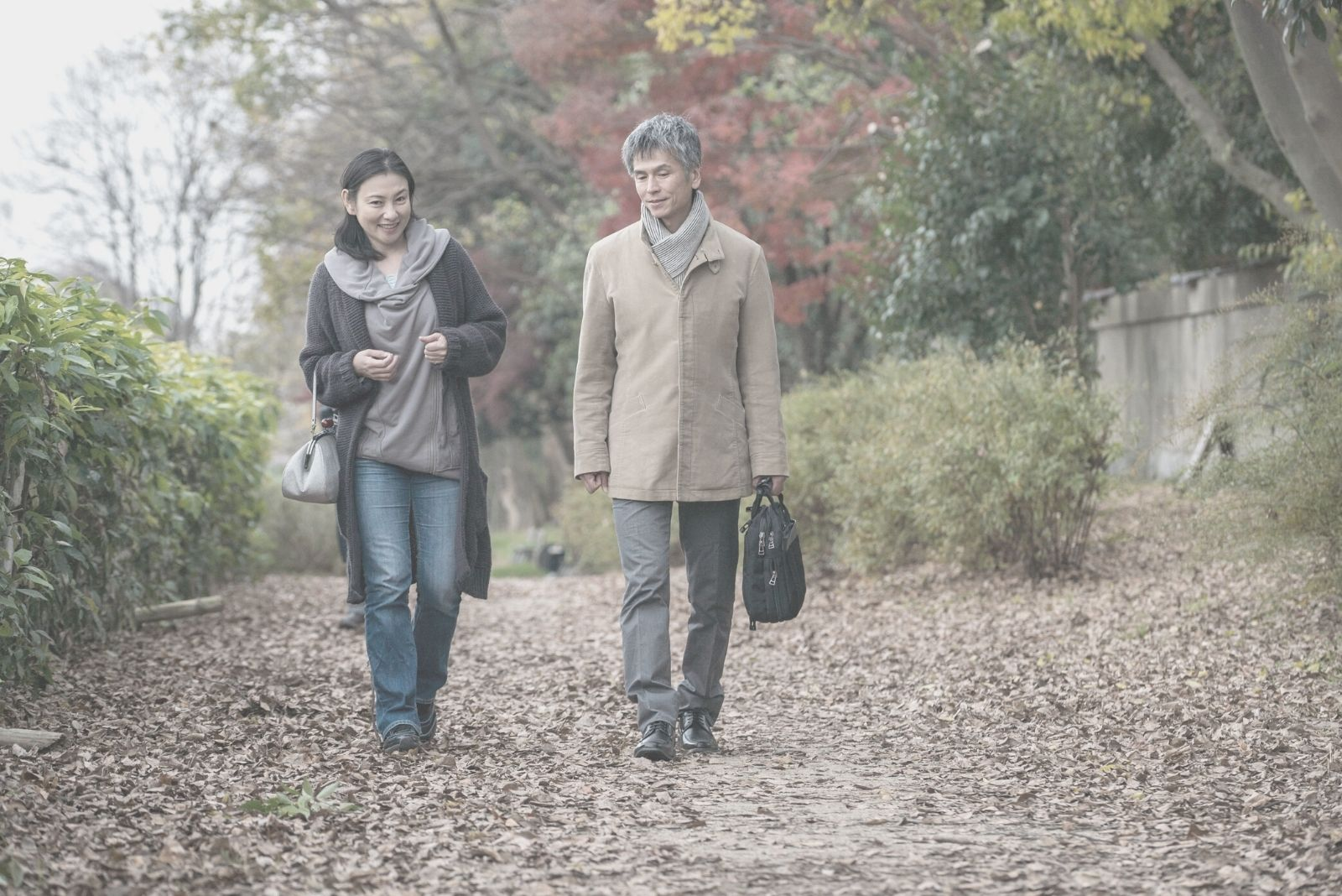 asian man and woman walking on the autumn park talking