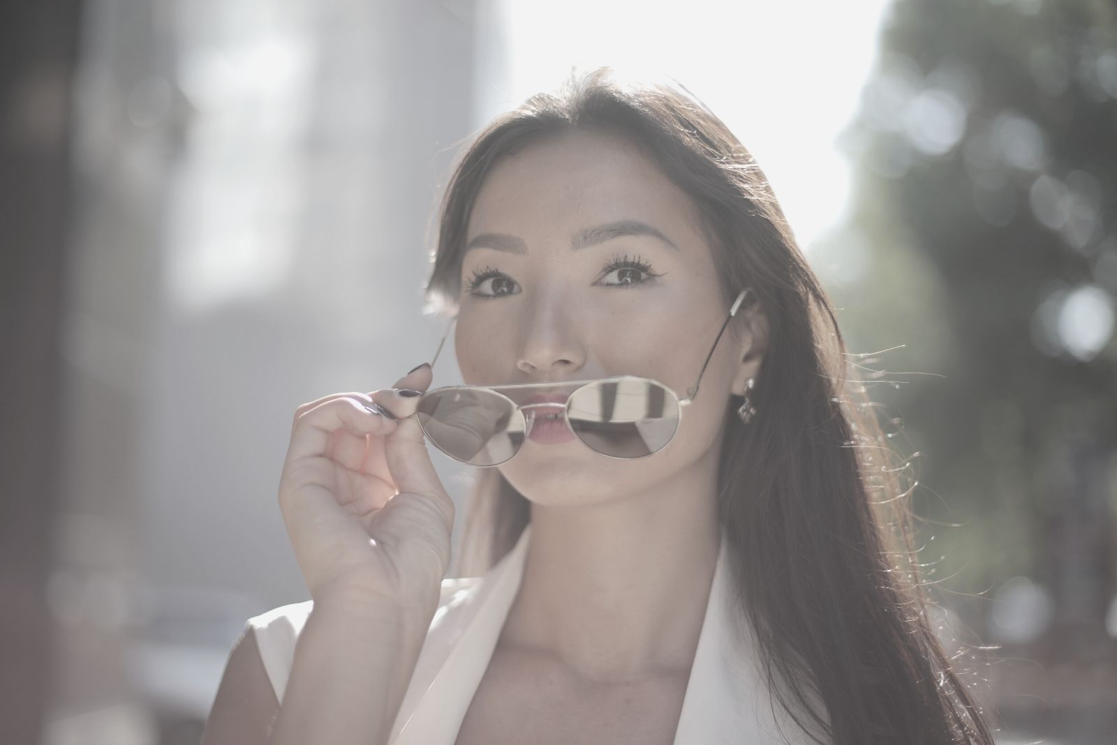 asian woman in white top holding a sunglass while walking outdoors