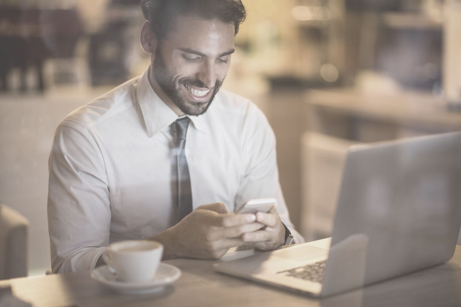 bearded man smiling reading messages from his phone inside a cafe with a laptop and coffee on table
