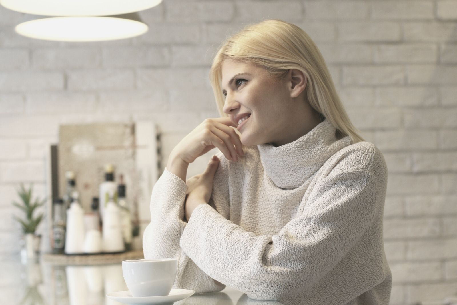 beautiful blonde woman smiling in the morning sitting on the kitchen counter smiling