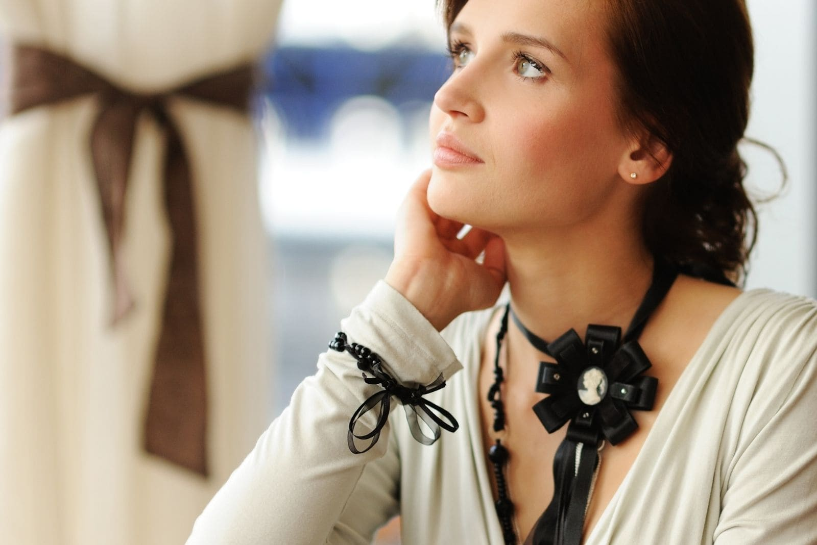 beautiful brunnette woman thinking deeply sitting and wearing a black ribbon