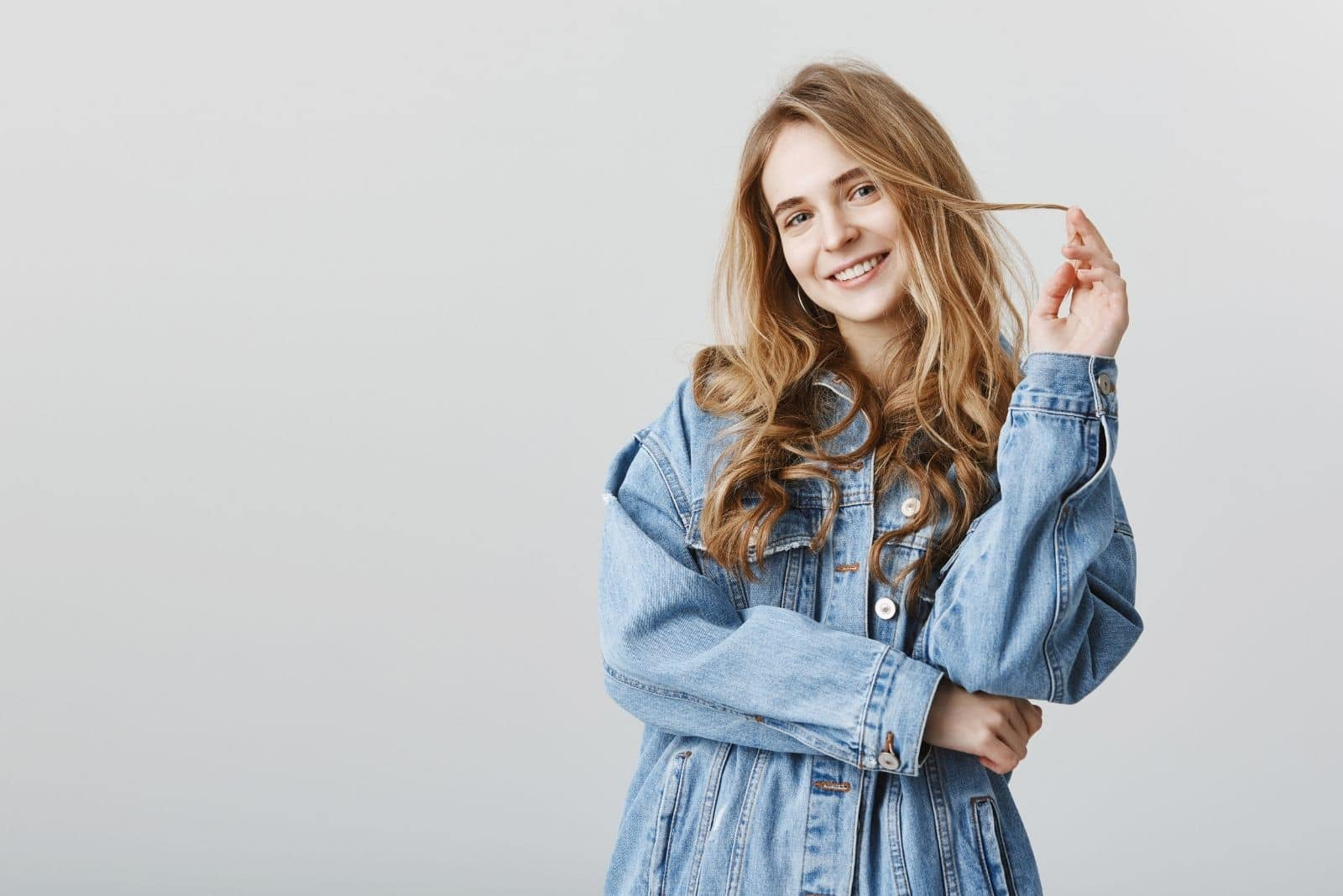 beautiful caucasian woman standing wearing oversized denim jacket and playing with her hair and smiling