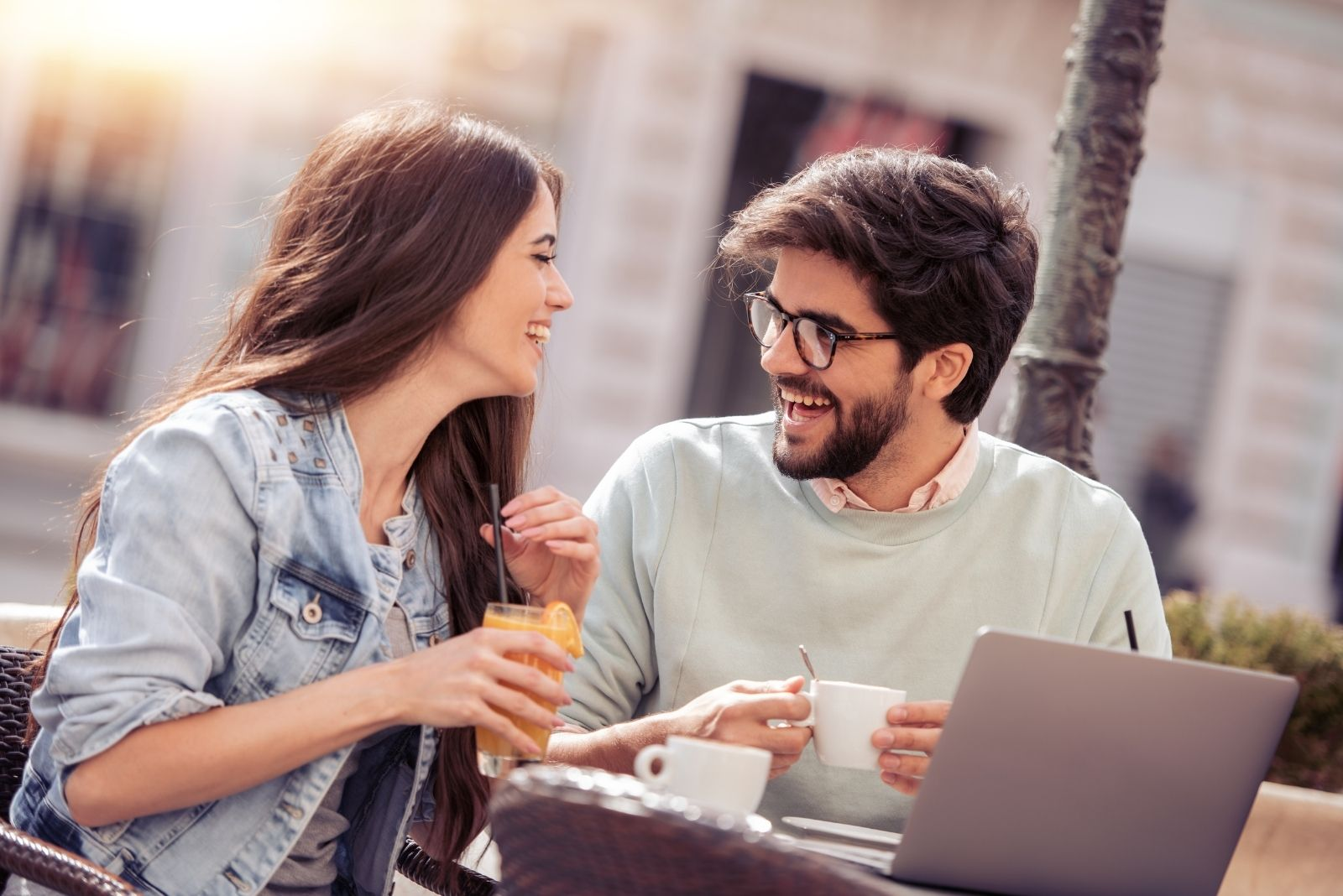 beautiful couple dating laughing and working at the same time in an outdoor cafe