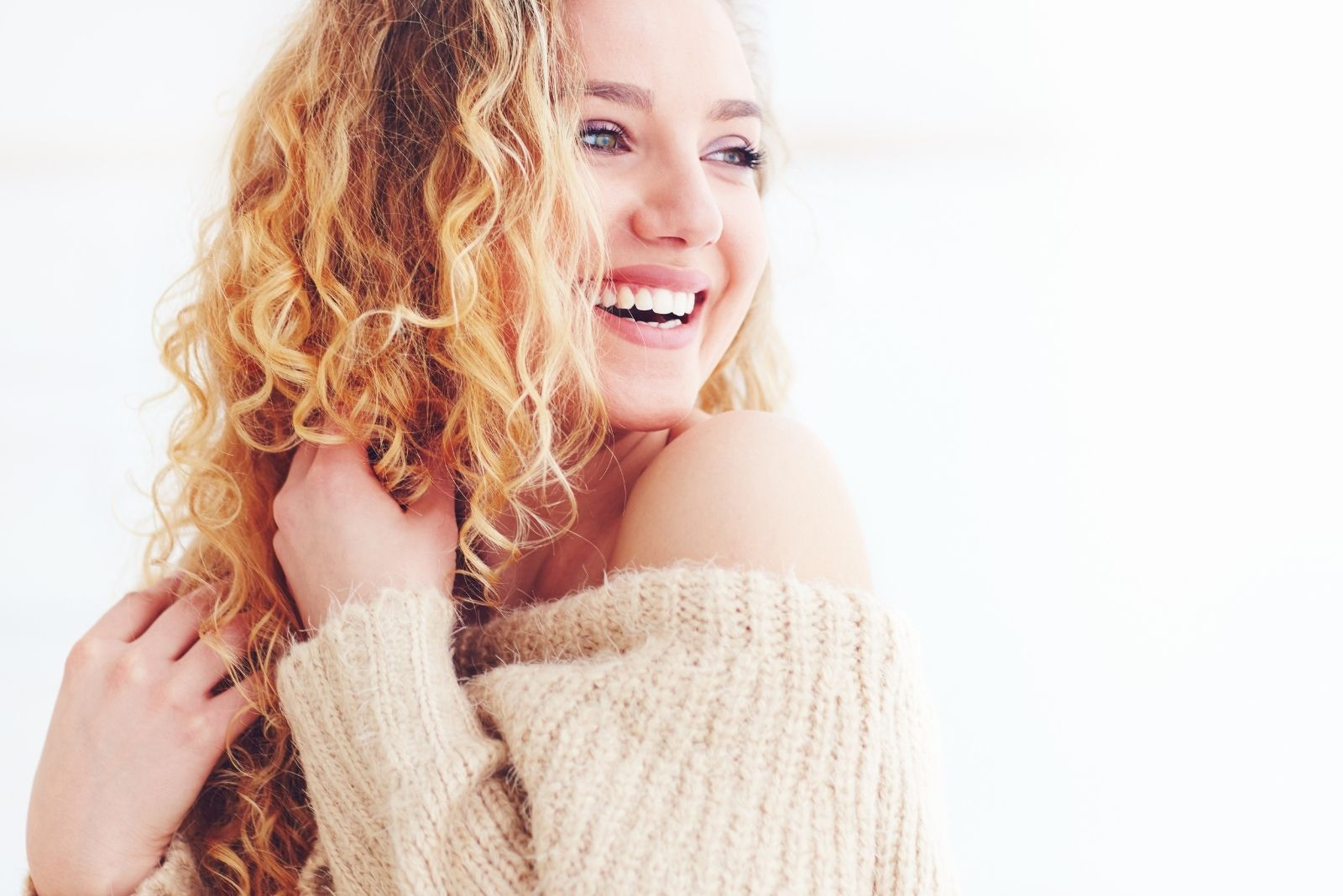 beautiful happy woman with curly blonde hair smiling