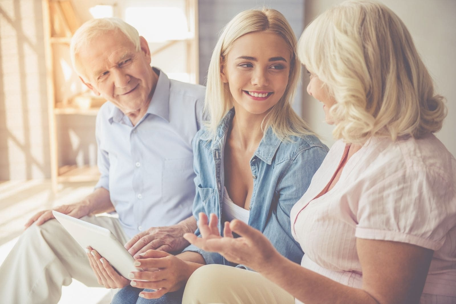 beautiful old couple with their daughter sitting and using digital tab while talking