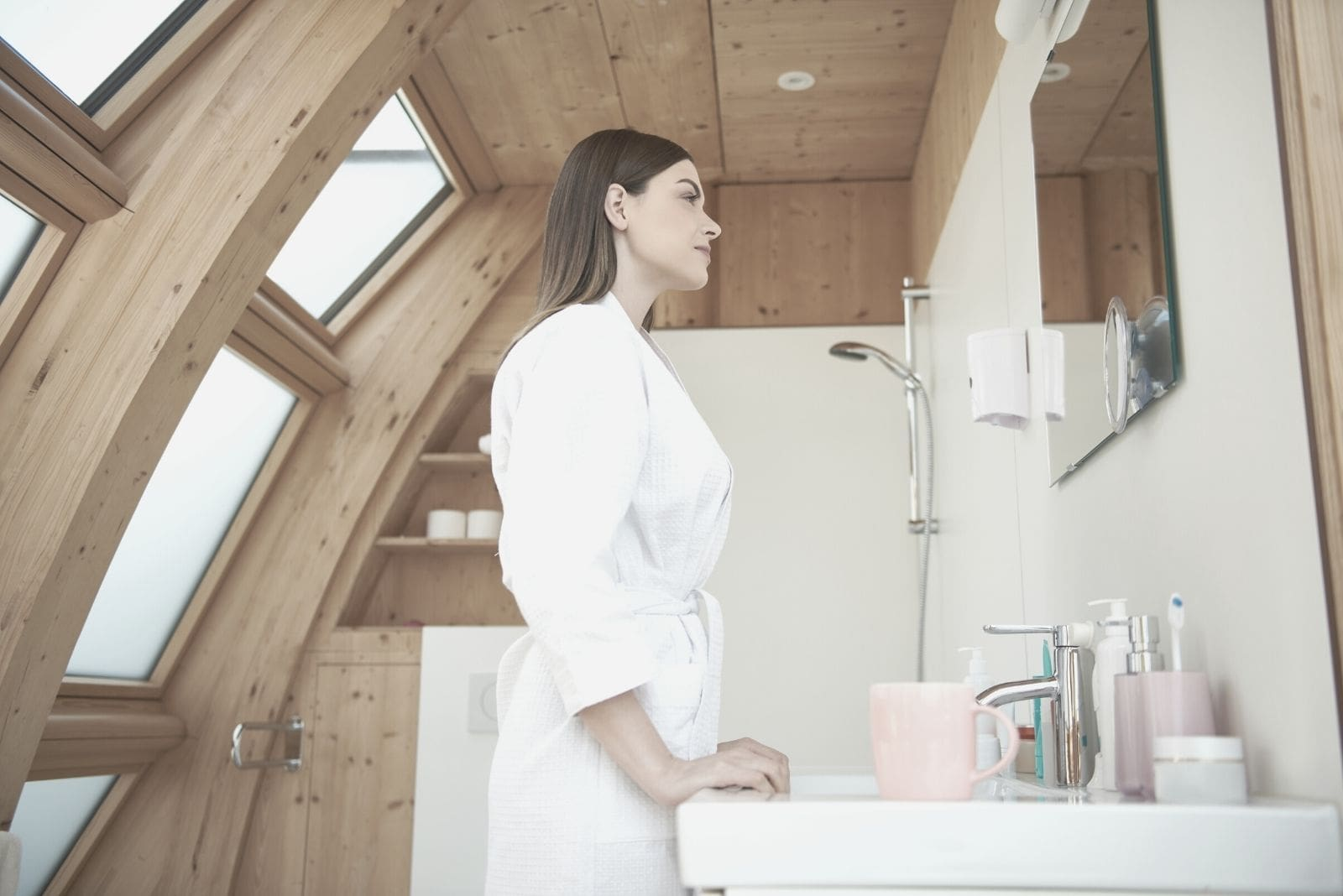 beautiful woman smiling and looking at the mirro inside the bathroom wearing a robe in sideview low angle