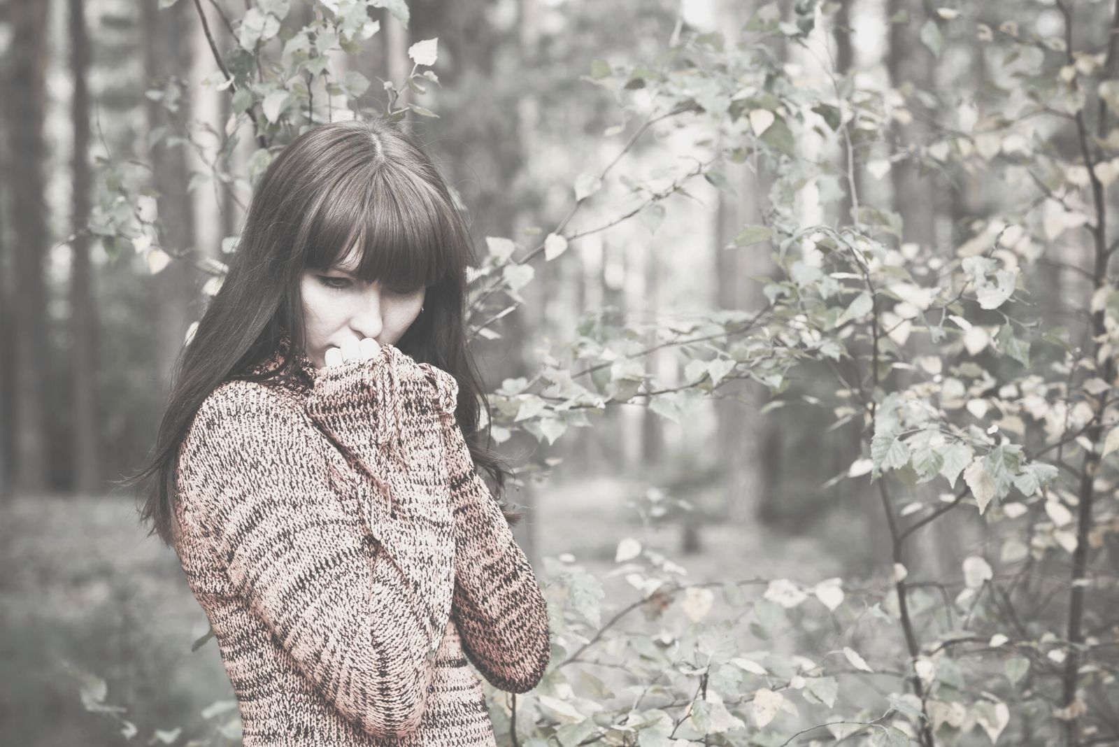 beautiful woman thoughtful wearing thick sweater standing in the forest during cold season