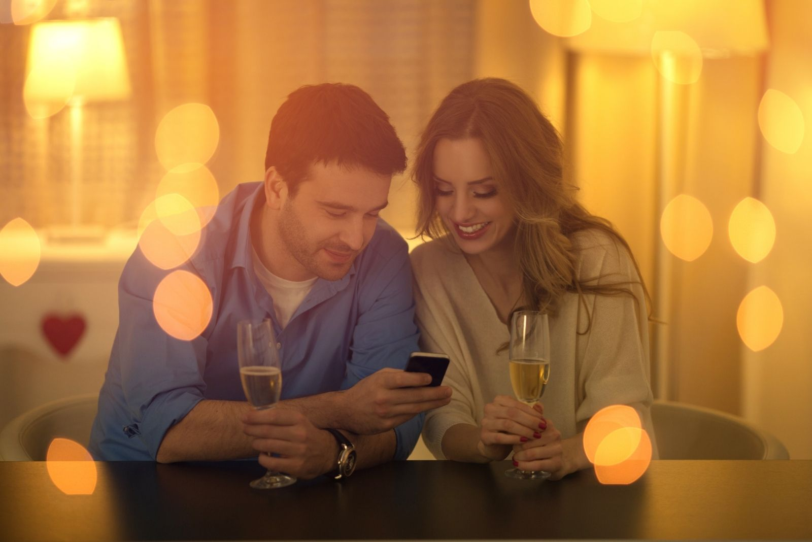 beautiful young couple looking at the smartphone during a date with lights in photographic effect