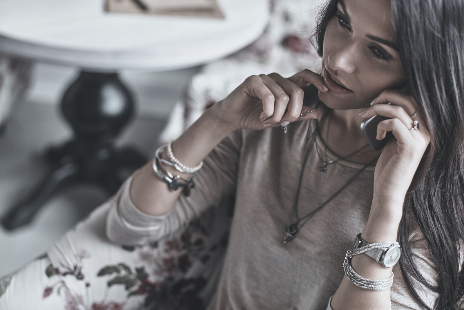 beautiful young woman touching her chin while talking on the the phone sitting on a couch indoors