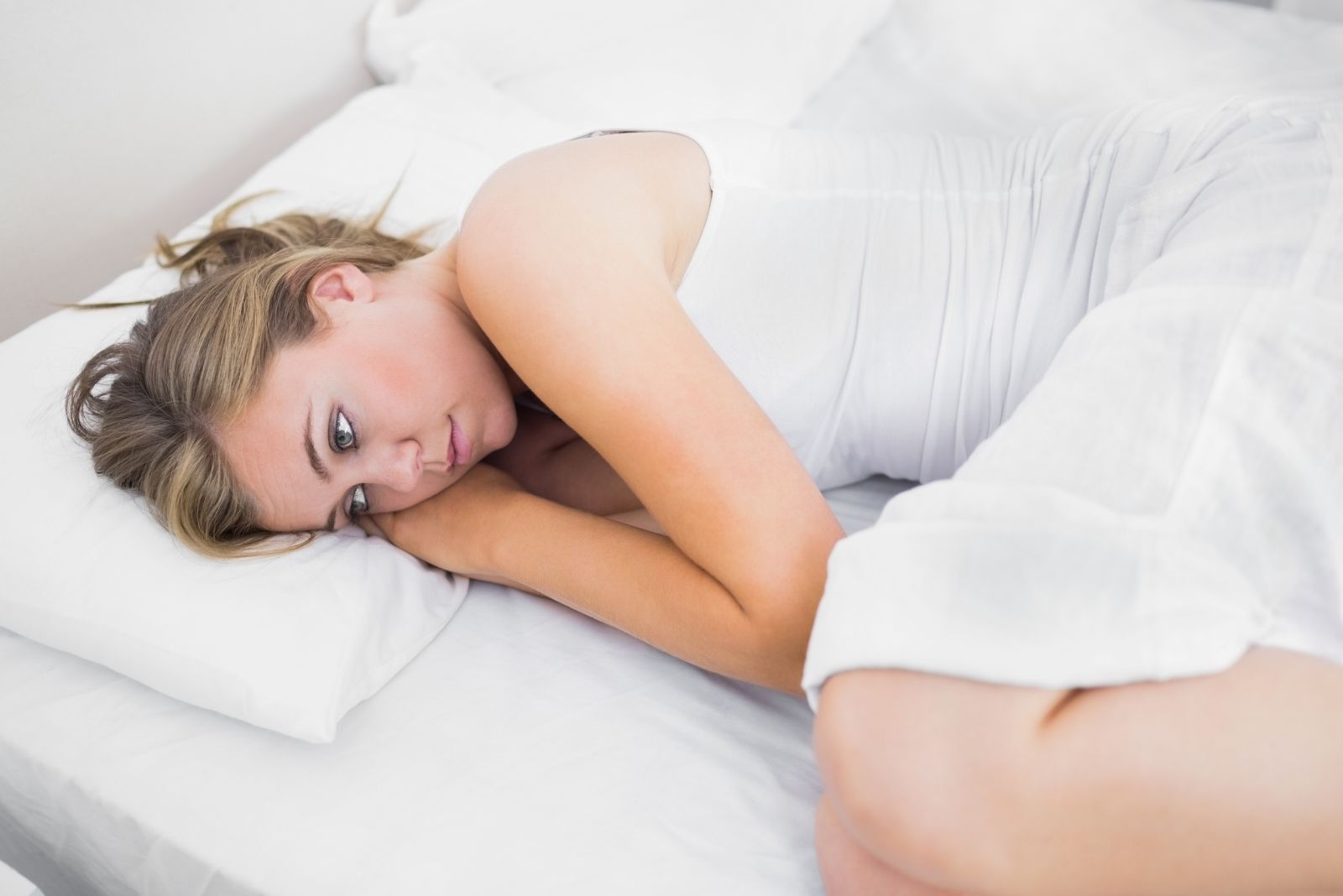 blonde woman thinking lying down in while linen wearing white dress
