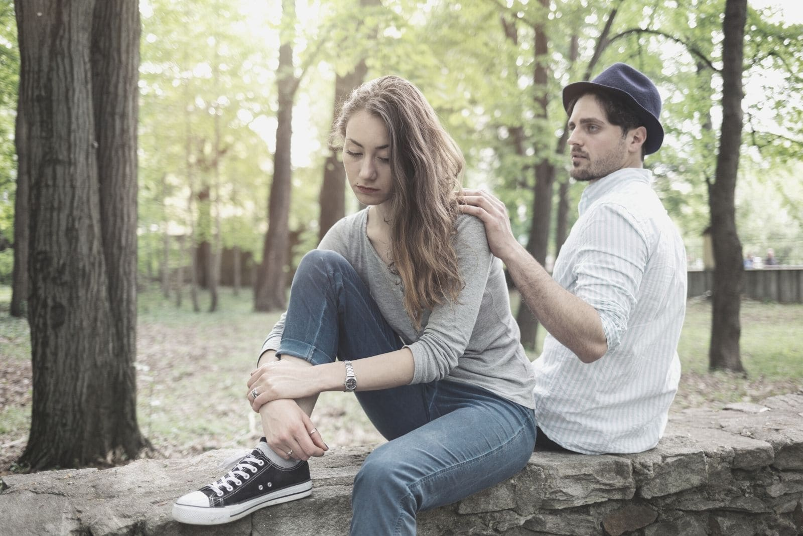 boyfriend looking worried tapping woman's shoulder breaking up while sitting in the bench in the park