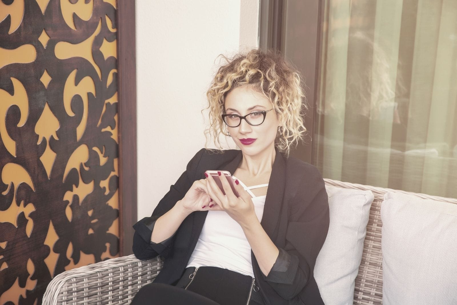 businesswoman social media concept of a woman with a phone and sitting indoors