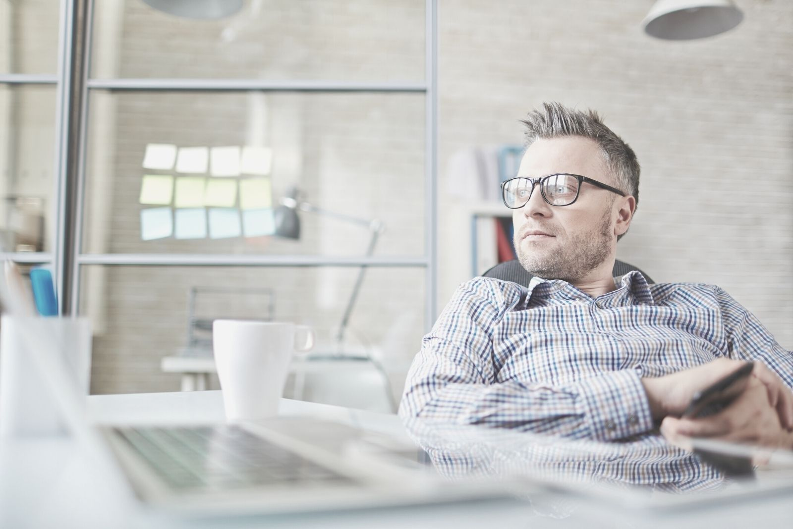 calm businessman sitting in the chair inside his office thinking deeply