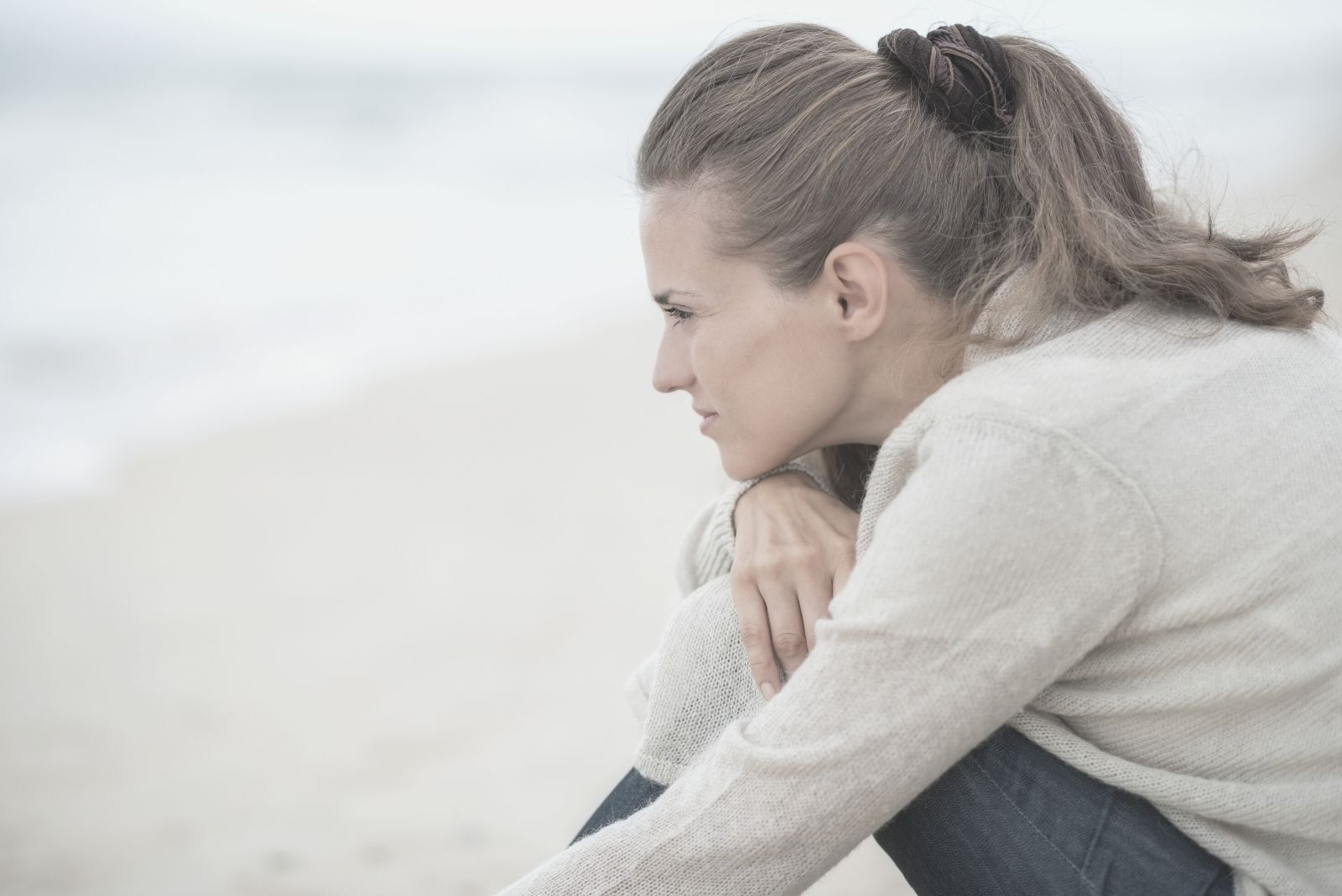 calm woman sitting on the beach contemplating
