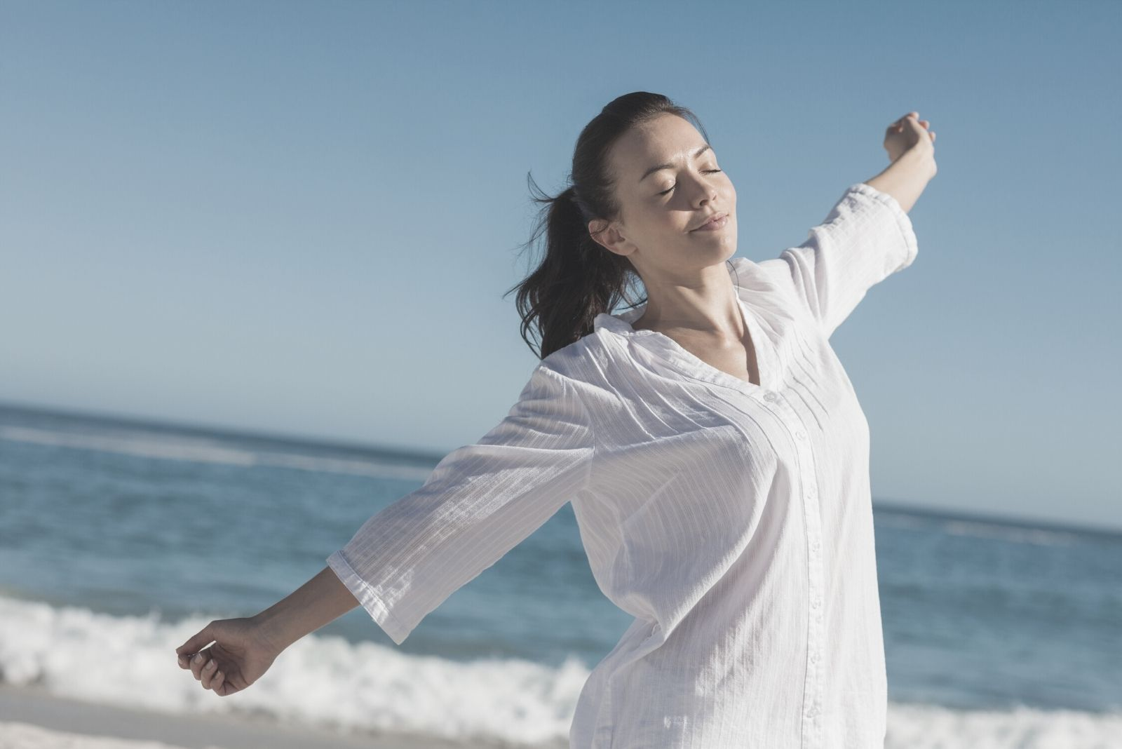 calm woman stretching in beach wearing white long sleeves and closing her eyes