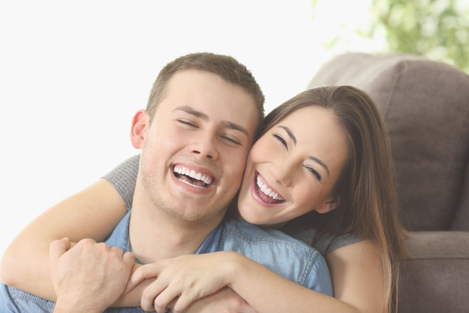 cheerful couple cuddling and hugging inside the living room