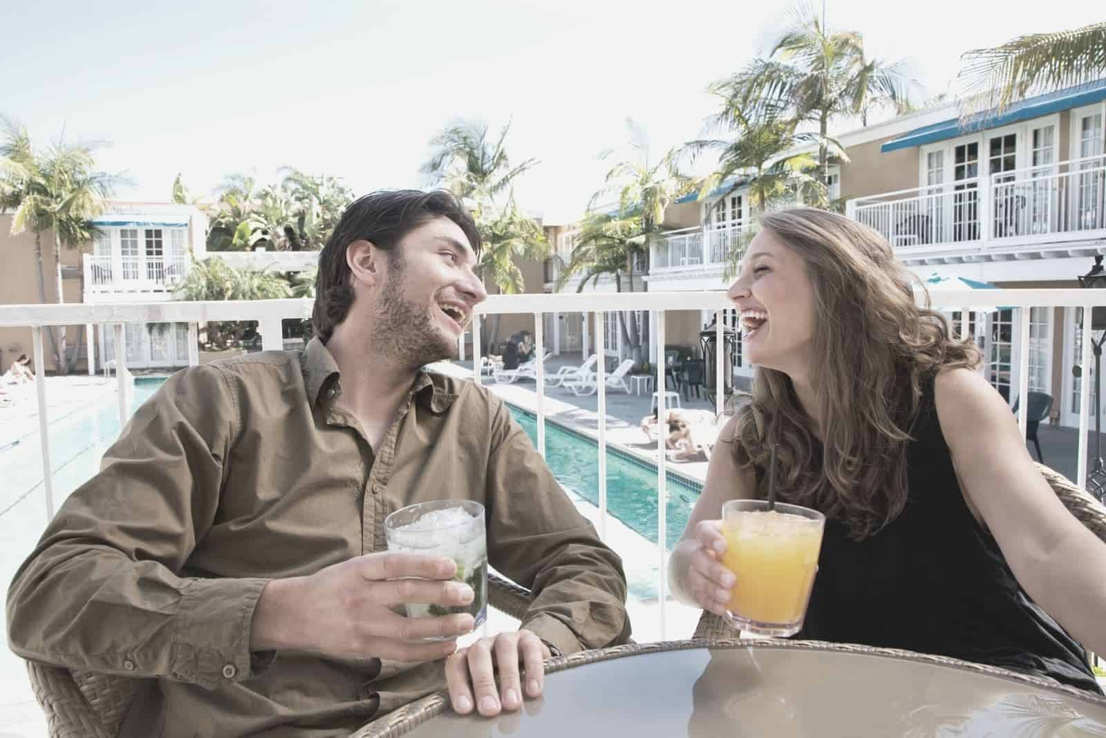 cheerful couple laughing while having a drinks and sitting by the table in a porch near a swimming pool