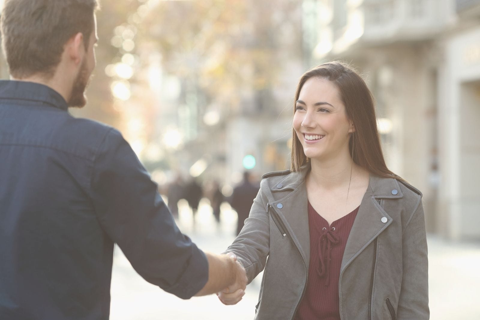 cheerful man and woman handshaking in a city street