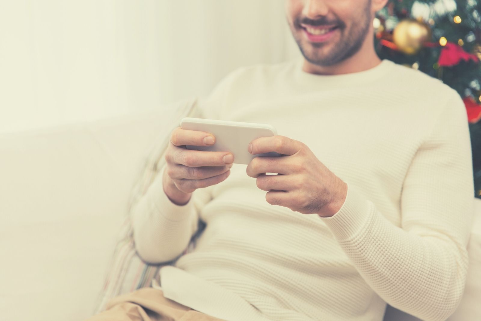 close up cropped image of a man texting and smiling inside home