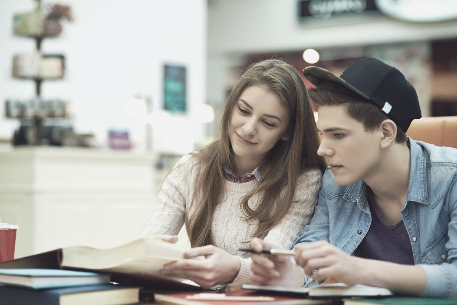 college couple studying inside the cafe with books on the table