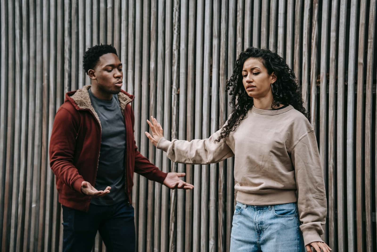 man and woman with curly hair arguing outdoor