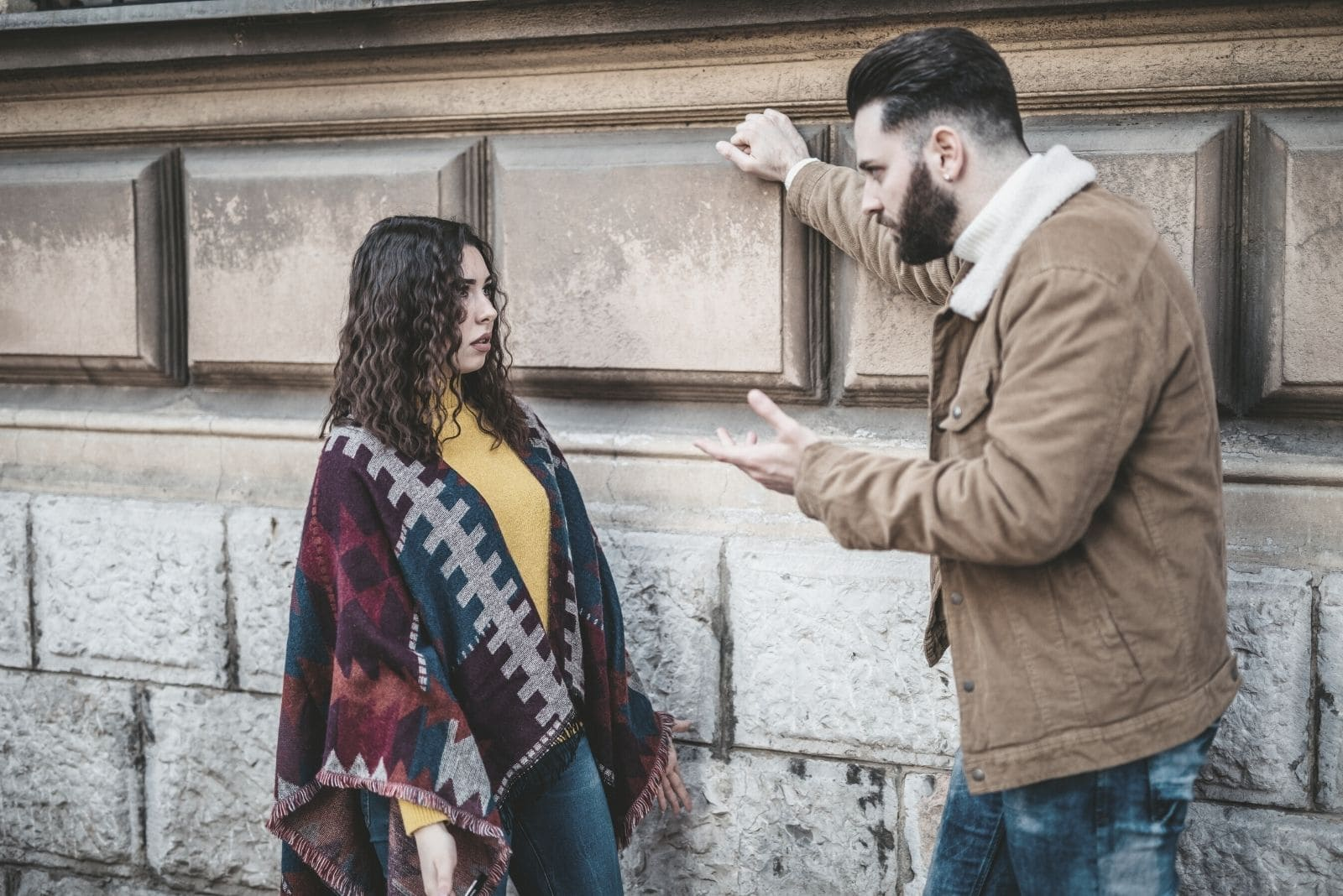 couple arguing outdoors near a large brick wall in the street