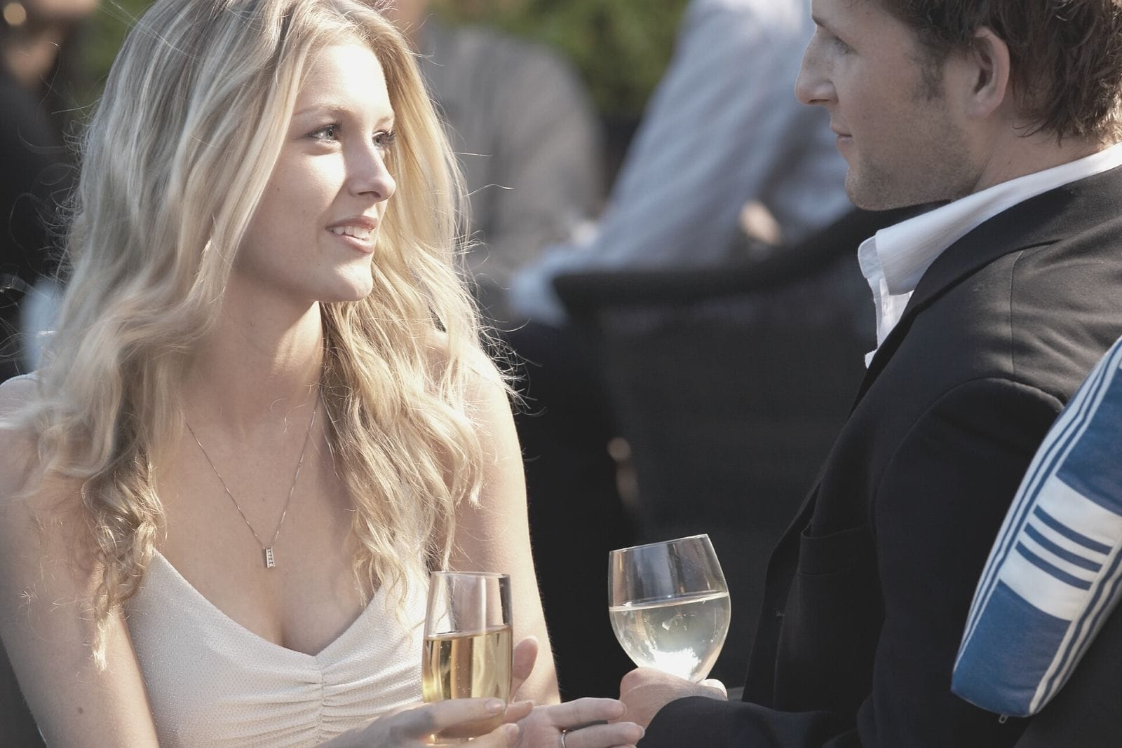 couple attending a party wearing formal dress and drinking wine