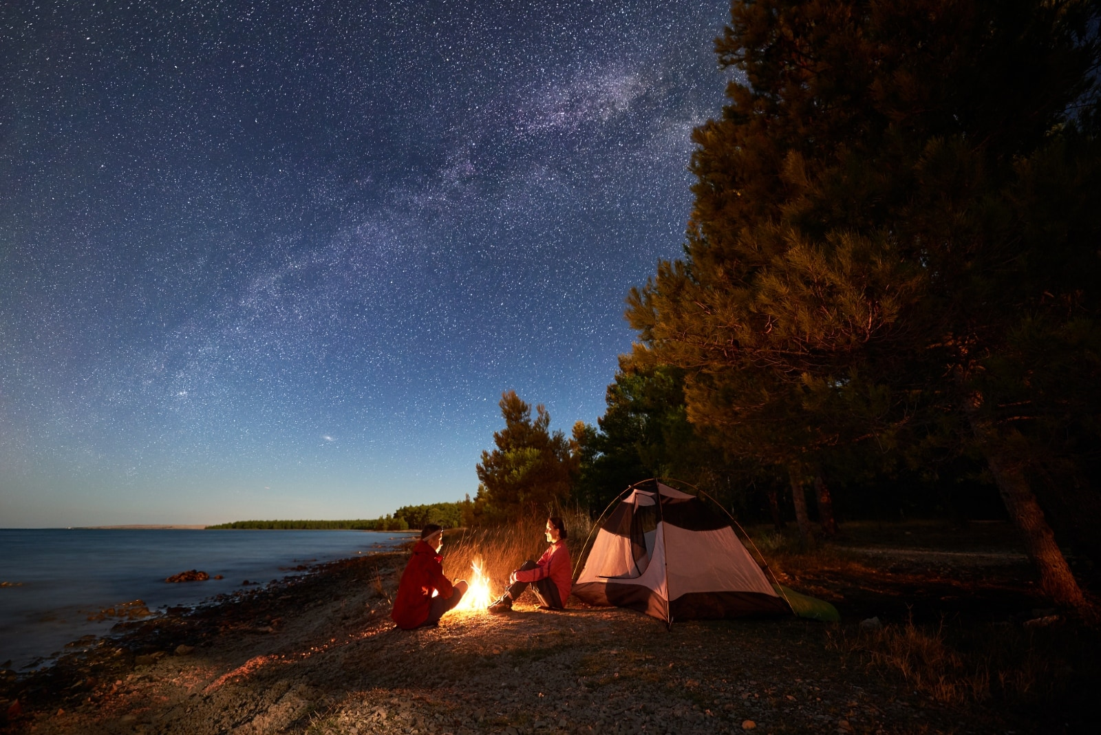 man and woman camping on shore during night