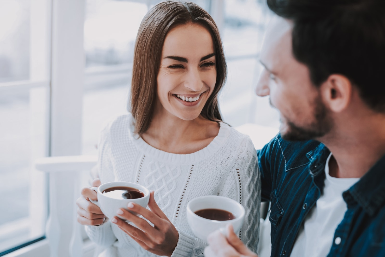 man and woman drinking coffee while sitting in cafe