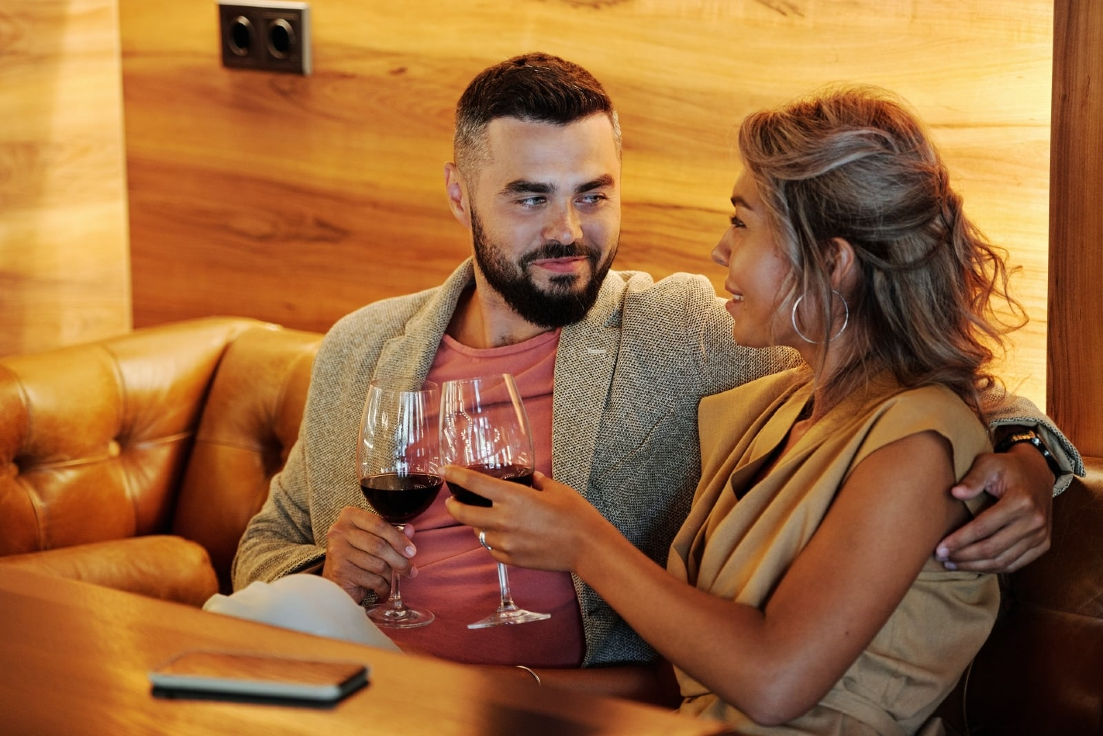 man and woman drinking wine while sitting in cafe