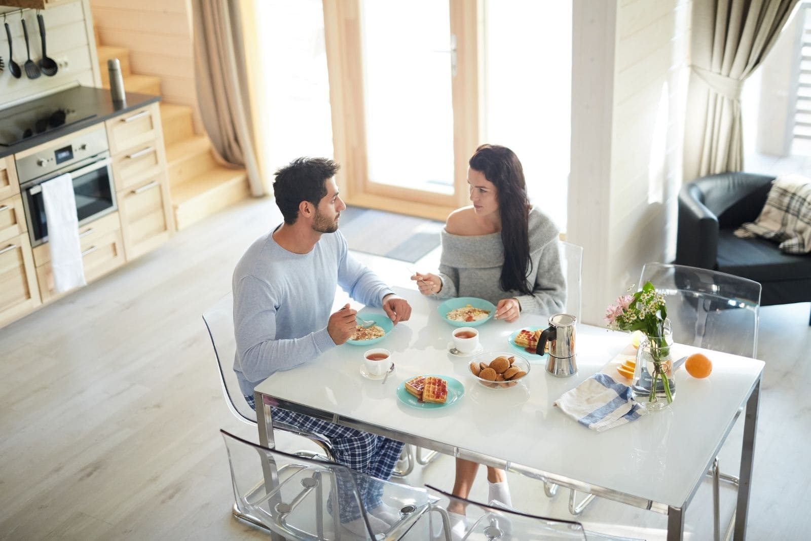 couple eating breakfast and talking seriously in a far low angle