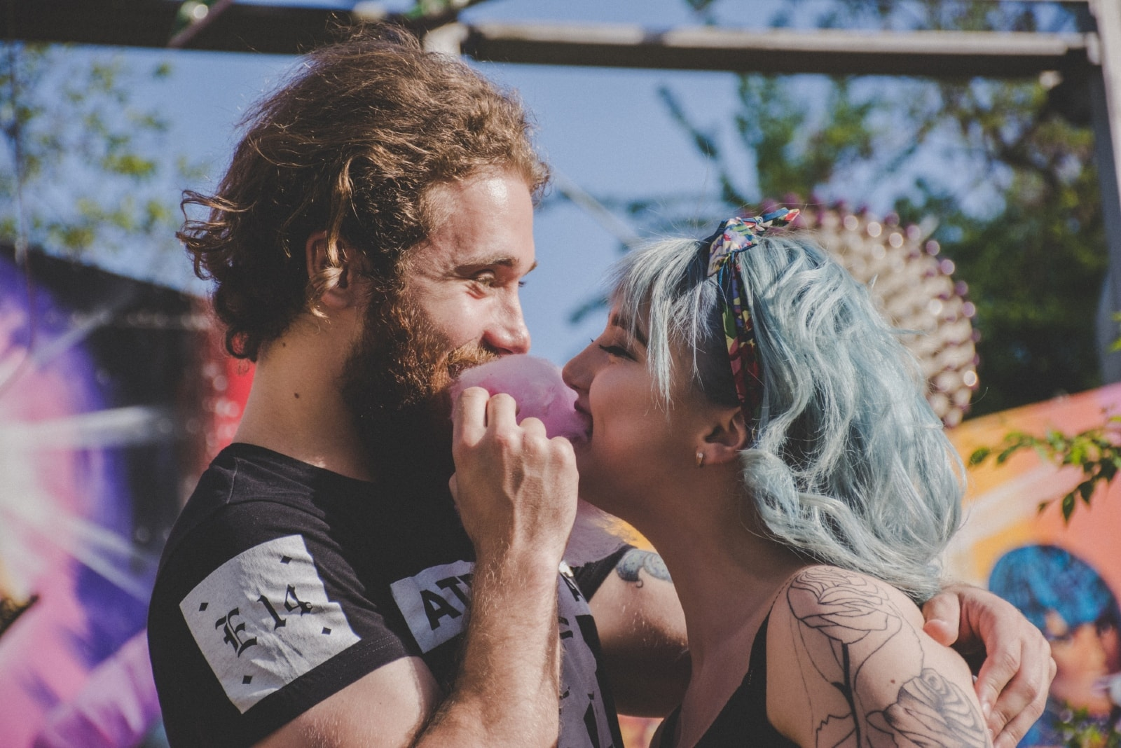 man and woman smiling while eating cotton candy