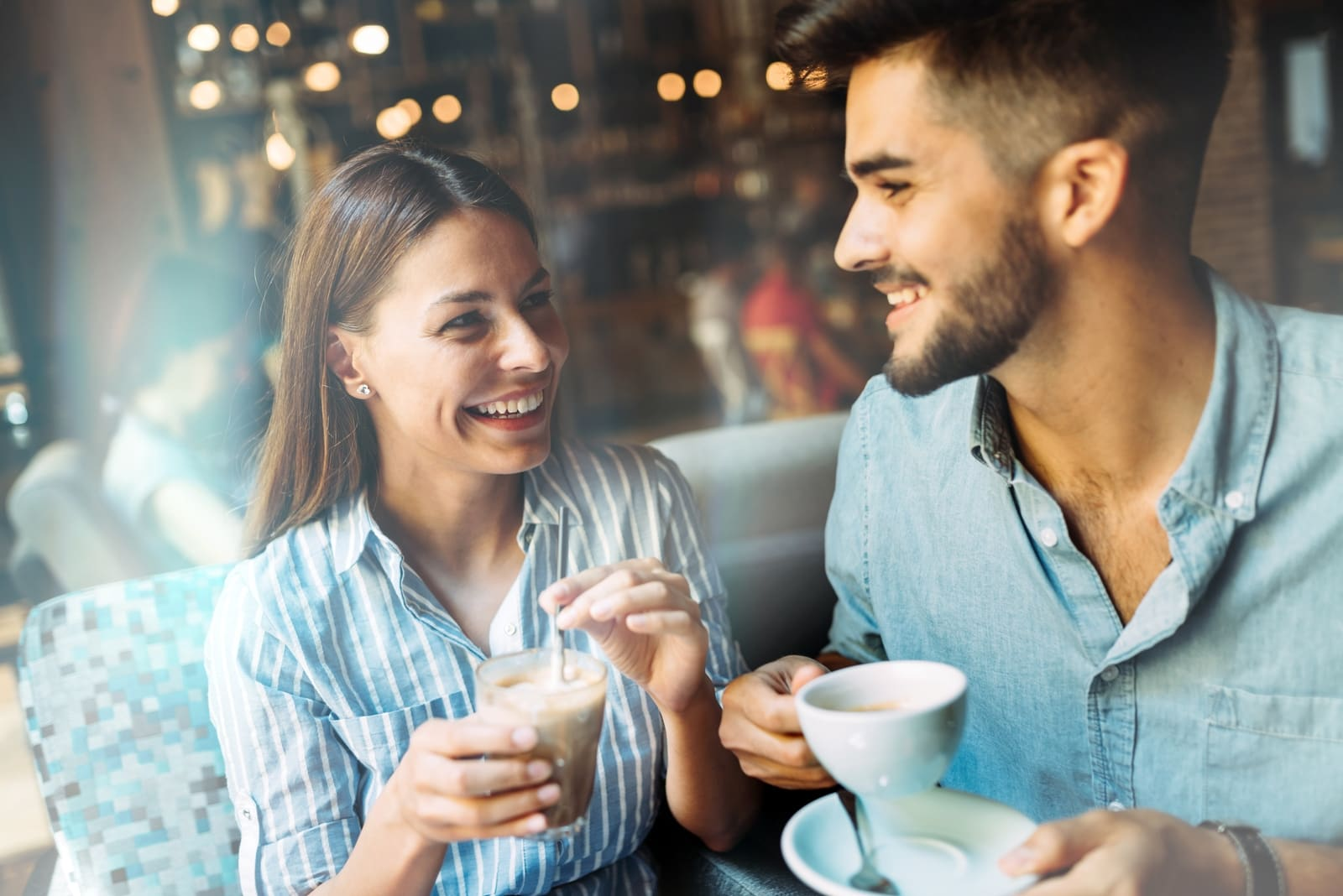 man and woman having coffee in cafe