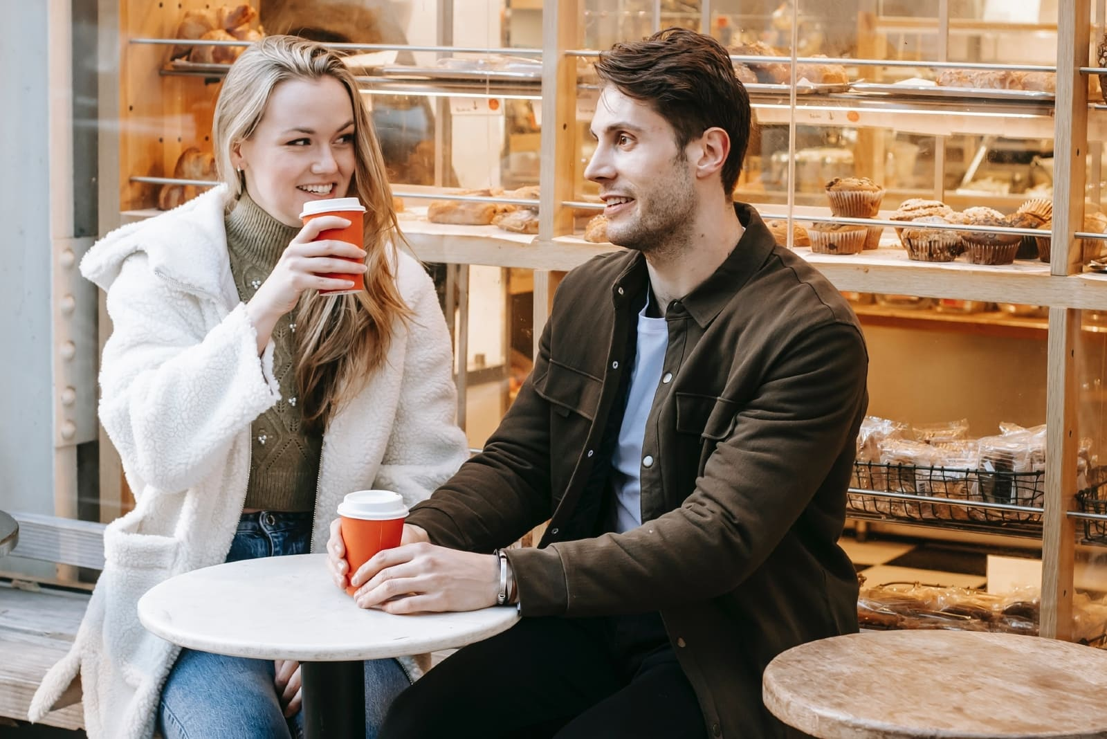 man and woman having coffee while sitting outdoor
