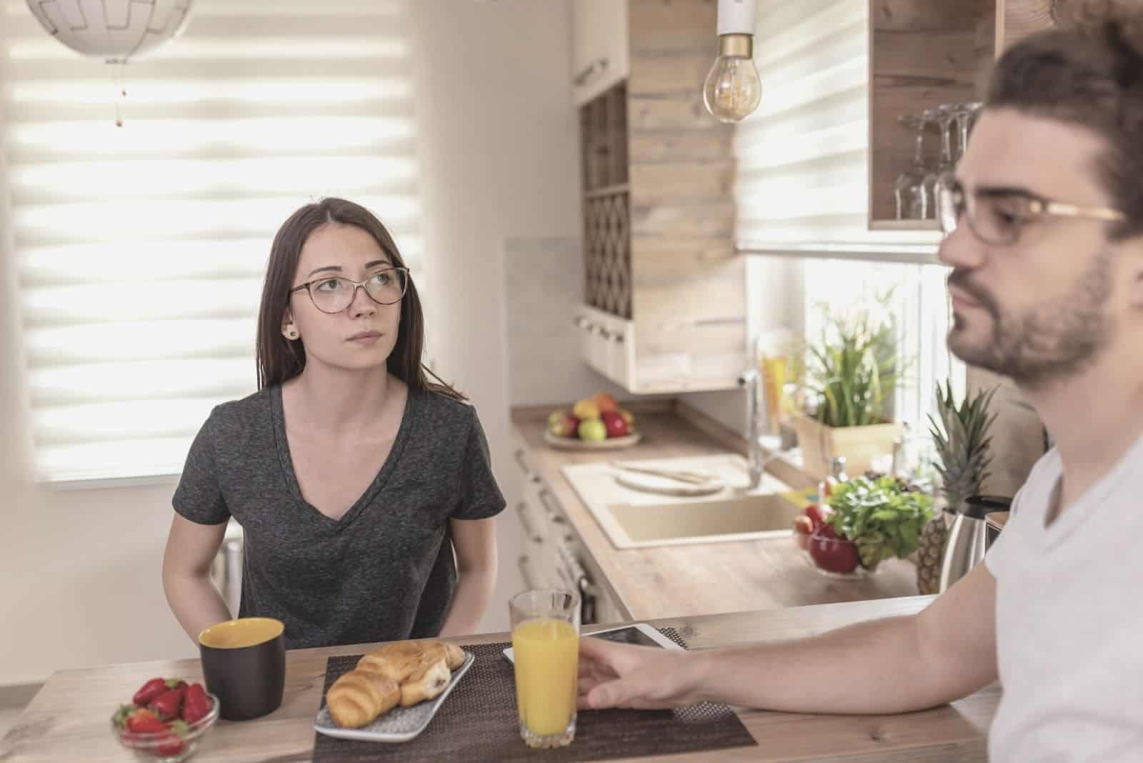 couple having serious conversation while having breakfast in the kitchen