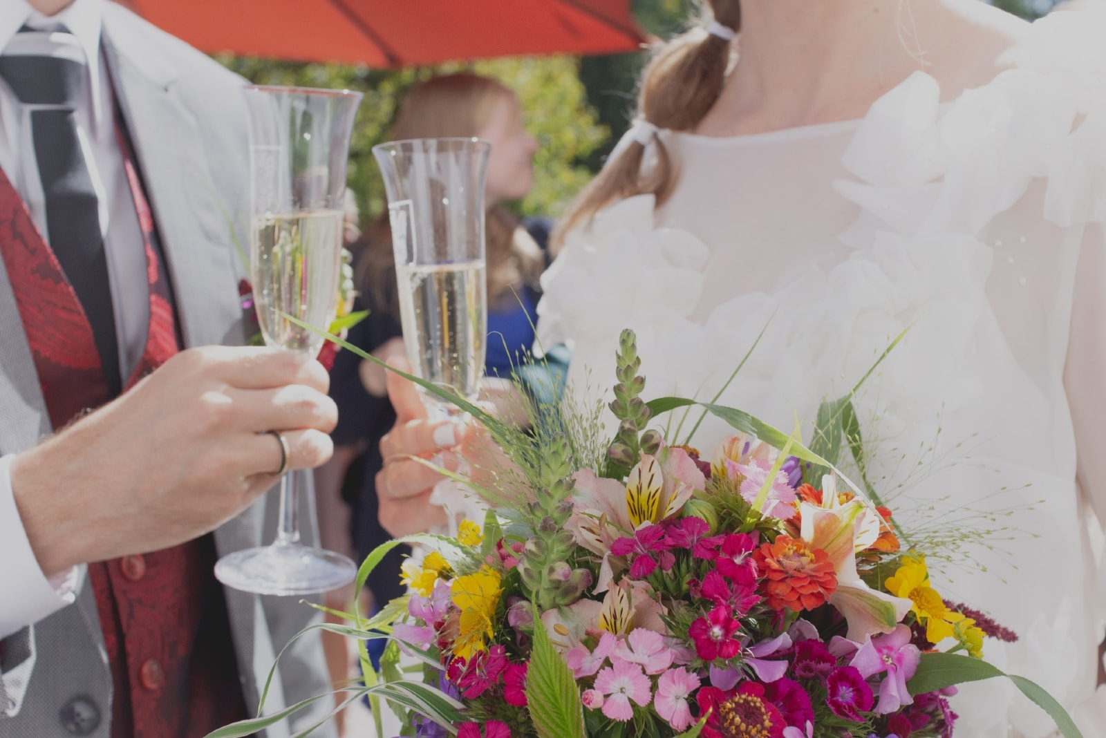 groom and bride holding glasses with champagne
