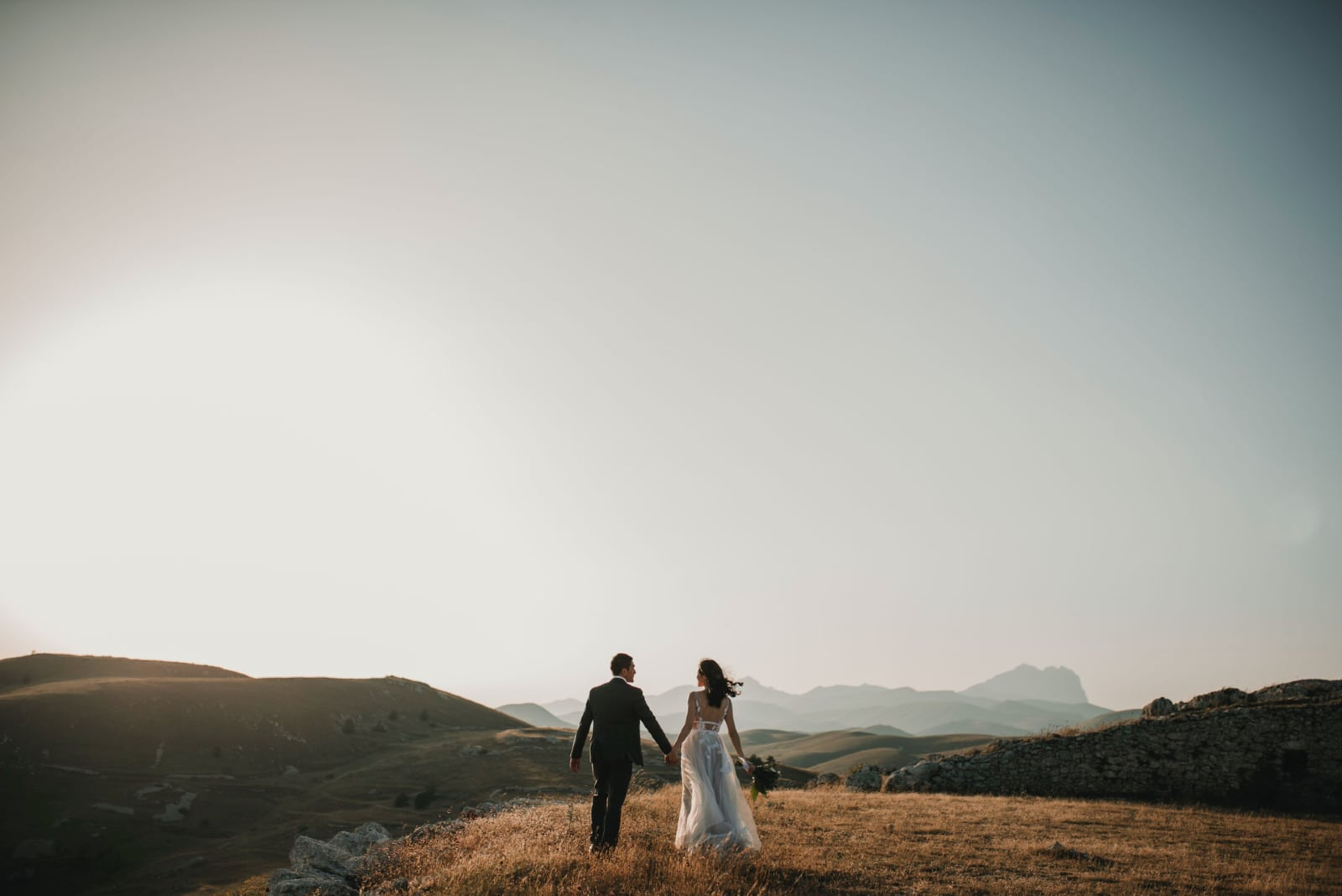 groom and bride holding hands while standing in the field