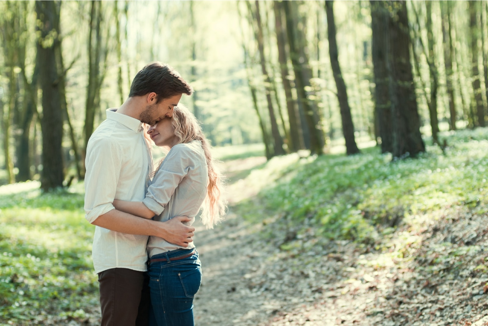 man and woman hugging while standing in park