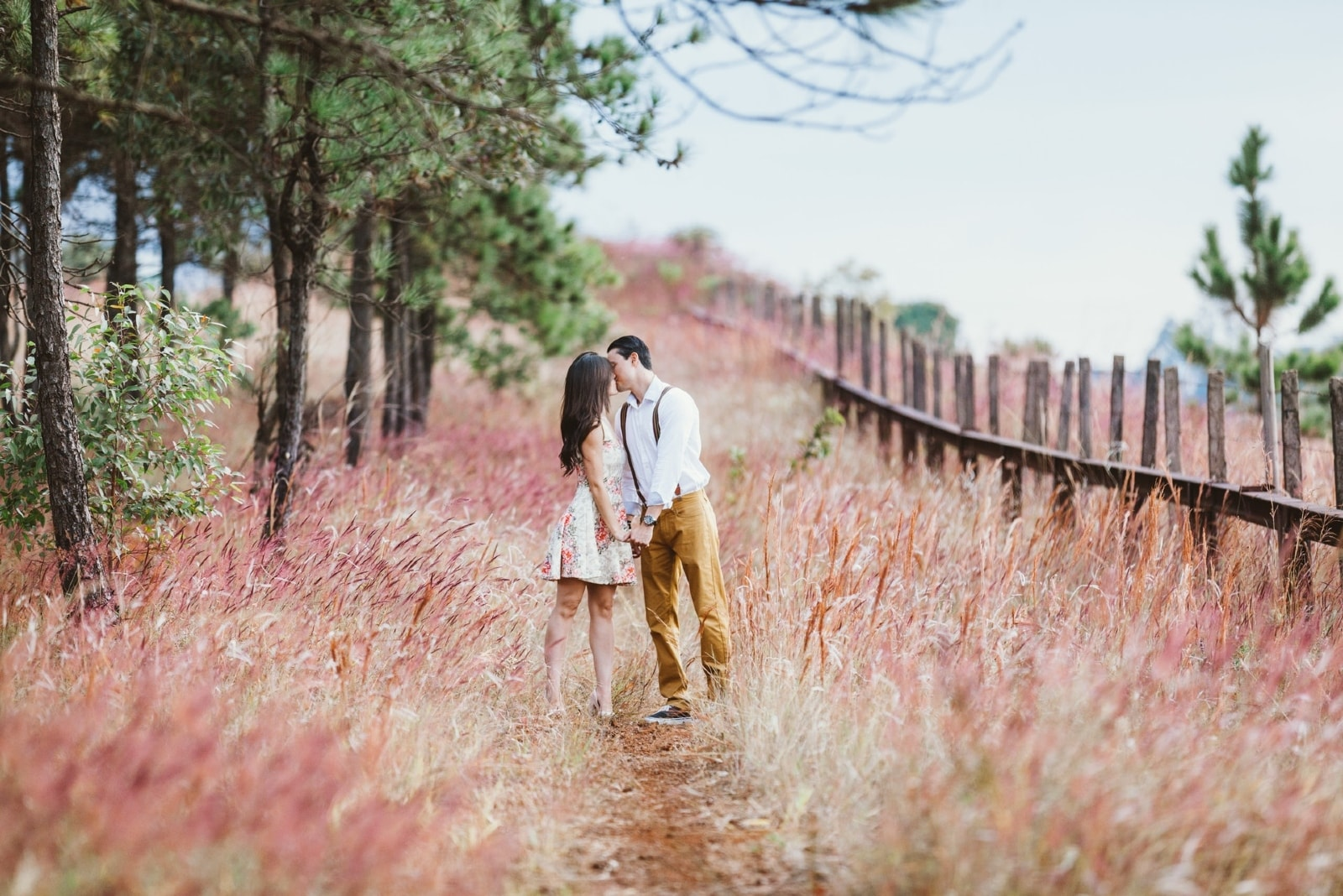 man and woman kissing while standing near tree