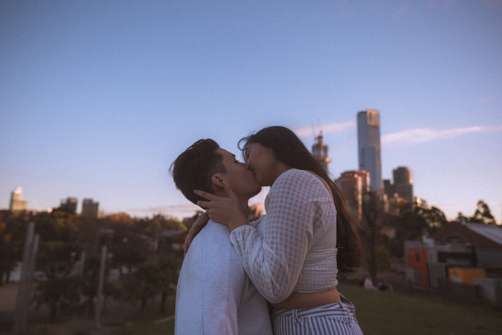 man and woman kissing while standing outdoor