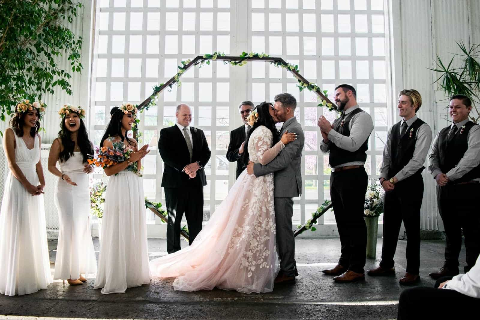 bride and groom kissing while standing near bridesmaids