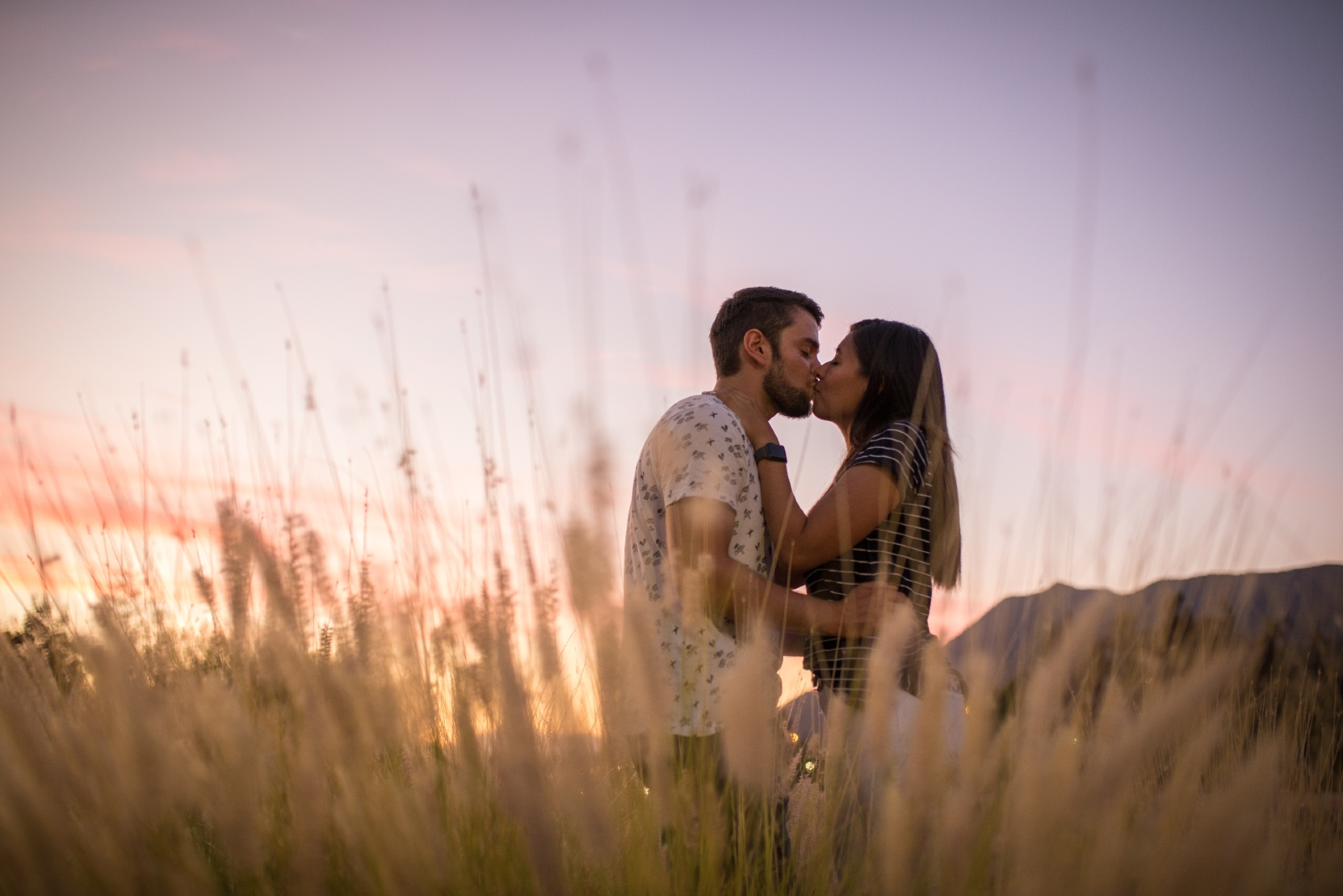 man and woman kissing while standing in the field