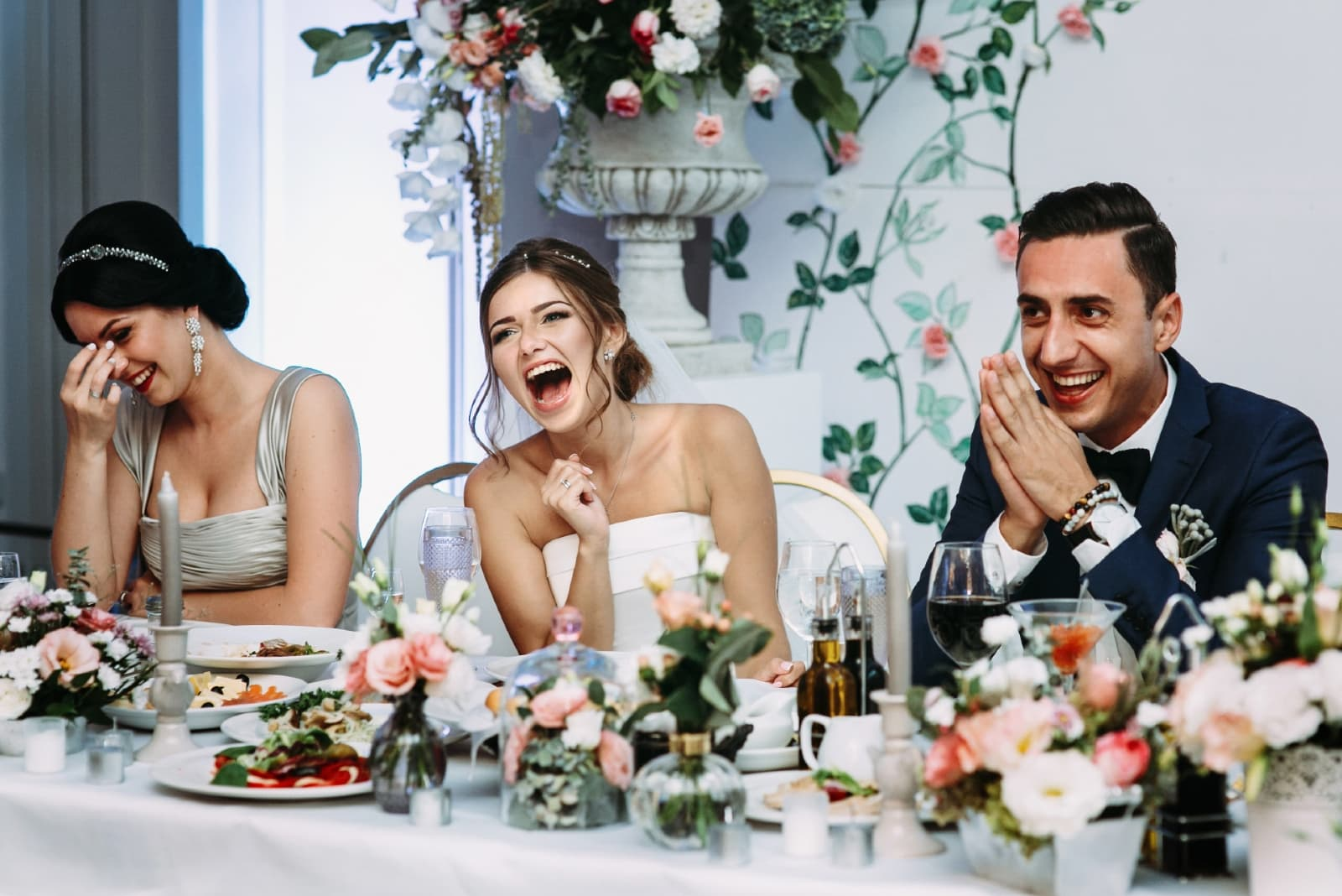 groom and bride laughing while sitting at table