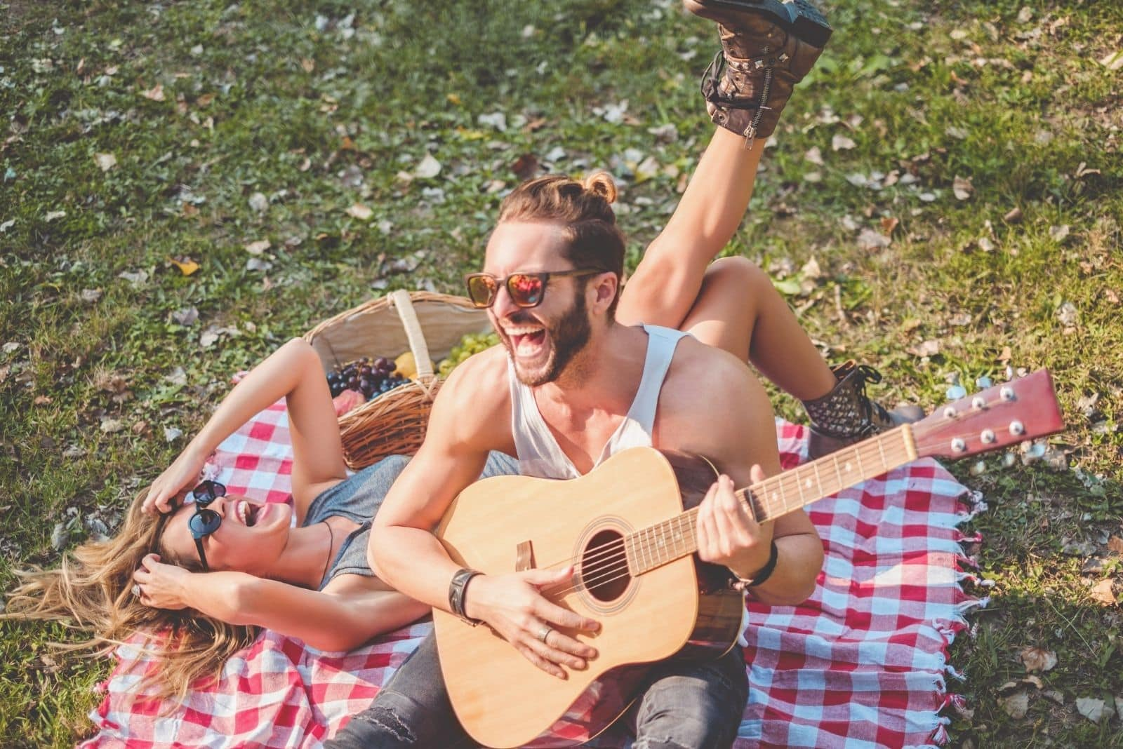 couple laughing on a picnic while man playing the guitar