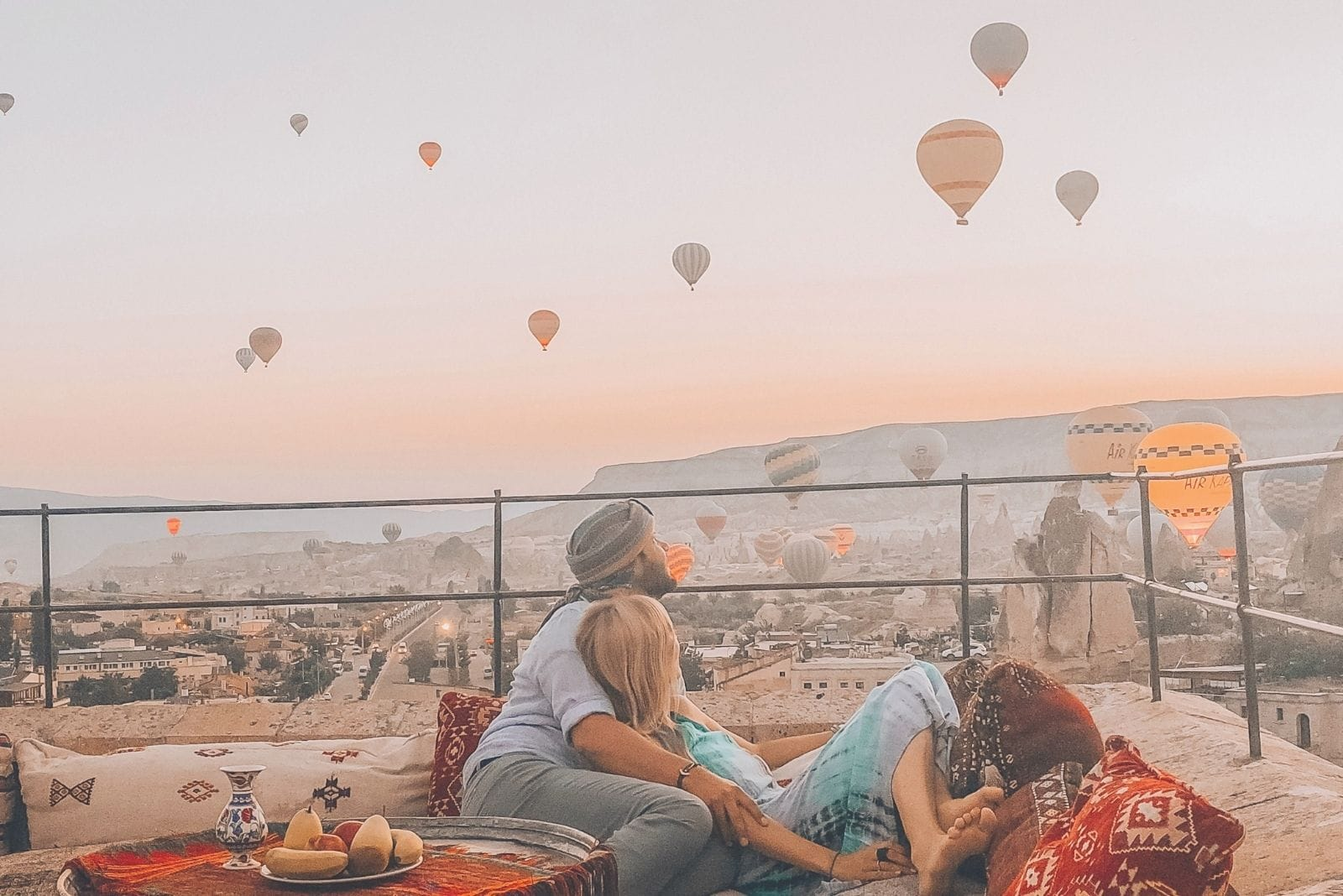 couple lying in sofa at the rooftop watching hot air balloons in the air